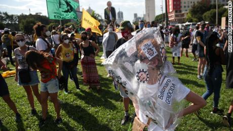 Un manifestante indossa uno striscione che accusa Bolsonaro di genocidio.