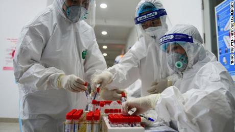 Gli operatori sanitari raccolgono campioni di tamponi per il test Covid-19 presso il centro medico del distretto di Thanh Xuan ad Hanoi il 15 maggio.
