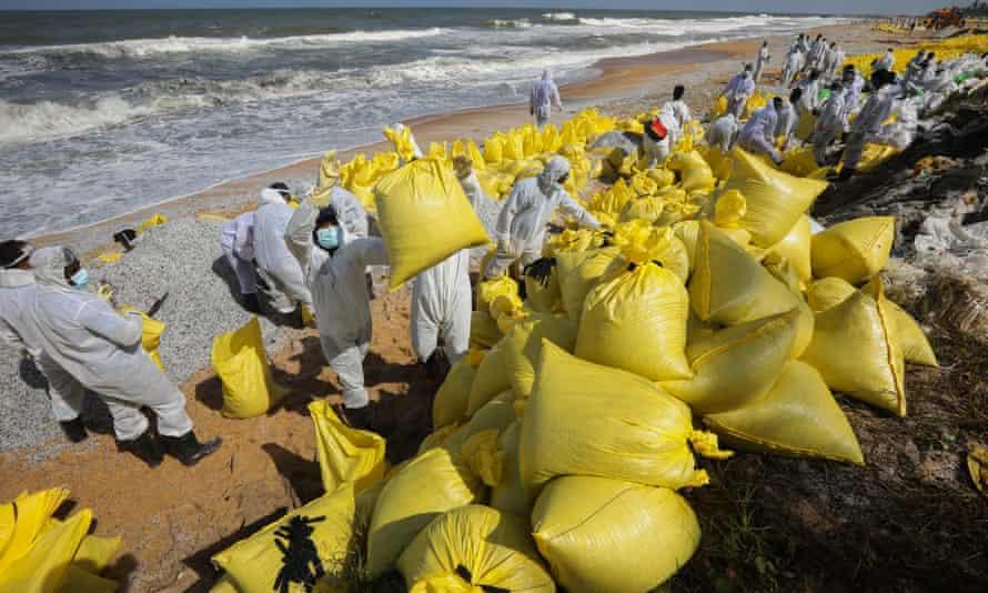 Personale della Marina dello Sri Lanka che indossa attrezzature per la pulizia su una spiaggia con sacchi gialli pieni di detriti